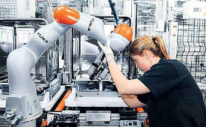 Woman and robotic machine work together inside industrial building.